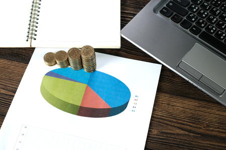 Step of coins stacks with notebook laptop computer and financial graph on white paper on working table, business planning vision and finance analysis concept idea. and copy space for add text.