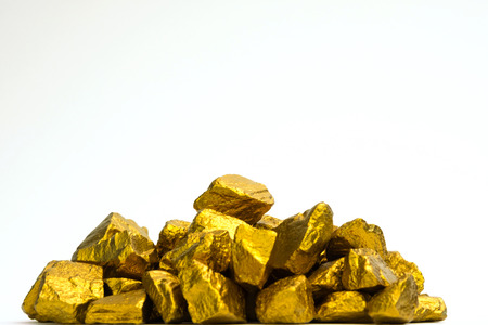 Foto de A pile of gold nuggets or gold ore on white background, precious stone or lump of golden stone, financial and business concept idea. - Imagen libre de derechos