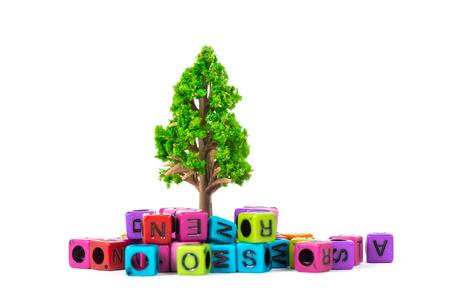 Foto de Pile of beads or letter bead with alphabet and little tree on white background. - Imagen libre de derechos