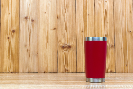 Photo for Red colour stainless steel tumbler or cold and hot storage cup on wooden background. - Royalty Free Image