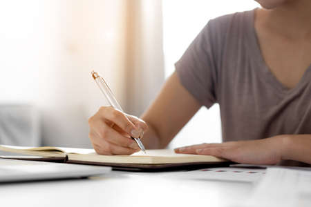 Photo pour Close up business women hand is writing notebook with laptop at home - image libre de droit