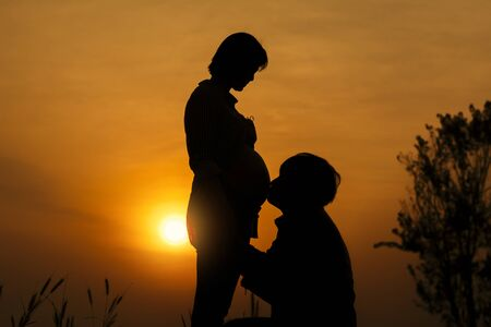 Photo pour Silhouette of Young man kissing his pregnant wife's belly and talking with their child on sunset background. - image libre de droit