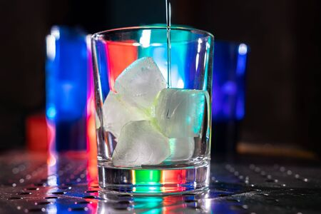 Photo for green cocktail with vodka gin rum sambuca tequila and pieces of ice on a bar in a nightclub with colored lights - Royalty Free Image