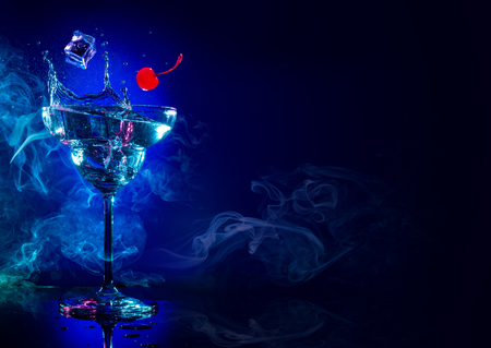 Foto de ice and cherry falling in a cocktail splash on blue smoky background - Imagen libre de derechos