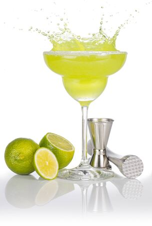 Photo pour bartender tools and lime fruits around a splashing margarita glass - image libre de droit