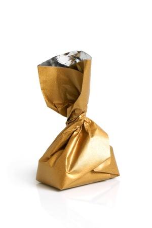 Photo pour Chocolate sweet in golden foil on a white background - image libre de droit