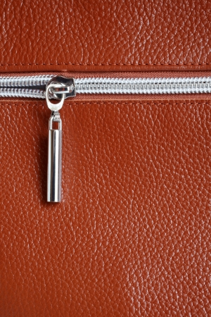 Brown leather with zipper background closeup, a vertical picture