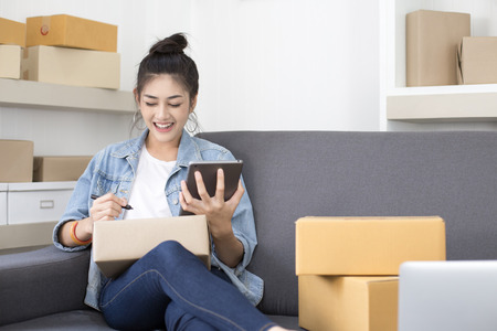 Foto de Young Asian Woman Working at home, Young Owner Woman Start up for Business Online, SME, Delivery Project, Woman with Online Business or SME Concept. - Imagen libre de derechos