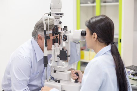 Photo pour Female doctor using machine for check old man eye. People with medical concept. - image libre de droit