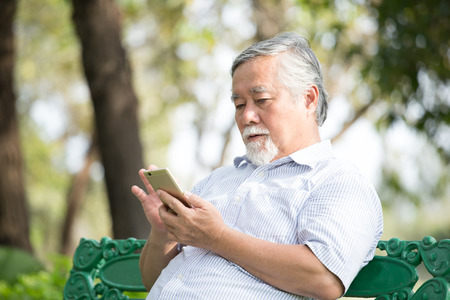 Elder people using smartphone with at park. People lifestyle concept.
