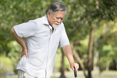 Photo pour Senior asian man suffering from back pain at outdoor place. Old man holding back because of lumbago - image libre de droit