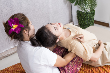 Beautiful young woman having her body with masseur in spa salon. Woman with thai massage. Woman with relax emotion.