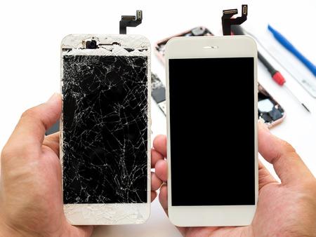 Foto de Close-up of cracked smartphone screen compare with new screen in technician hand on blurred smartphone component background  - Imagen libre de derechos