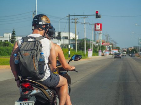 Chiang Rai, Thailand: November 23, 2018 - Couple foreign backpack traveler wearing helmet parking motorcycle for red traffic light on the road in Thailand. Driving or riding safty concept