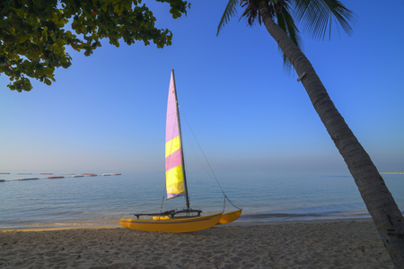 Sail boat on tropical beach with blue water background at Pattaya