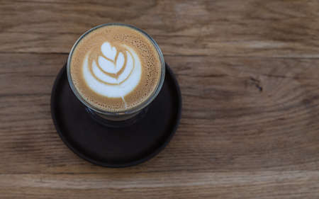 Photo pour Cappuccino with latte art in glass cup on wooden table in cafe or coffeehouse. Selective focus. - image libre de droit