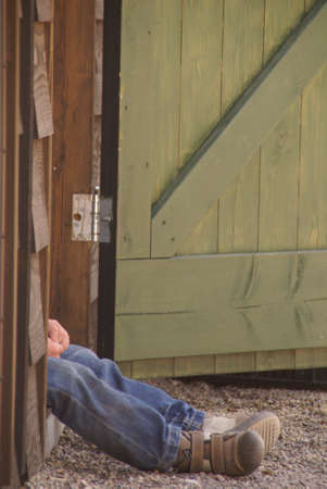 tired boy with jeans, sitting in the doorway of a barn