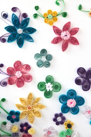 Flowers made of paper in different colors on a white background