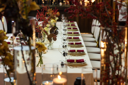 Photo pour table setting in a restaurant decorated with napkins on plates and flowers and candles - image libre de droit