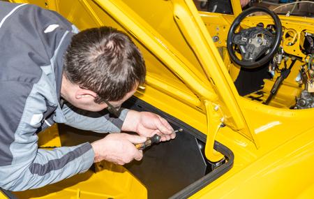 Photo pour Car mechanic screws car parts together again after restoration - Serie Repair Workshop - image libre de droit