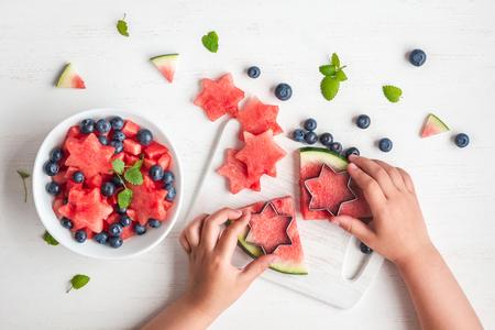 Photo pour children's hands cooking salad on white table, top view, flat lay - image libre de droit
