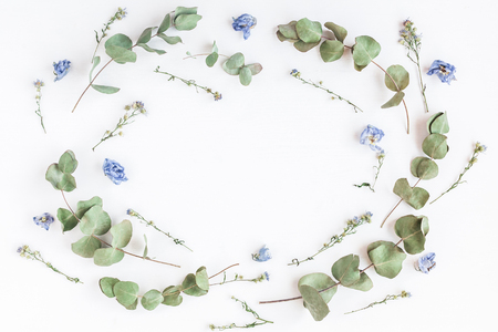 Flowers composition. Frame made of dried flowers and eucalyptus branches on white background. Flat lay, top view