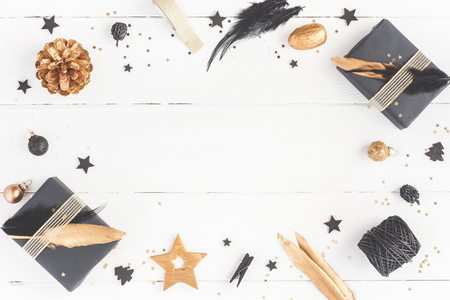 Foto de Christmas composition. Christmas gifts, pine cones, black and golden decorations on white wooden background. Flat lay, top view, copy space - Imagen libre de derechos