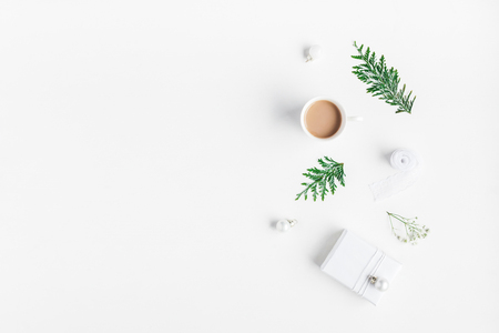 Christmas composition. Cup of coffeee, christmas gift, thuja branches on white background. Flat lay, top view, copy space