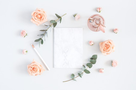 Wedding invitation card. Marble paper blank, rose flowers, eucalyptus branches on gray background. Wedding concept. Flat lay, top view, copy space