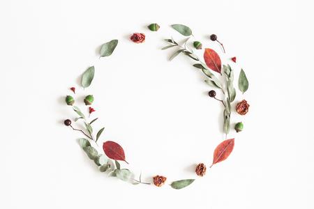 Foto de Autumn composition. Wreath made of eucalyptus branches, rose flowers, dried leaves on white background. Autumn, fall concept. Flat lay, top view, copy space - Imagen libre de derechos