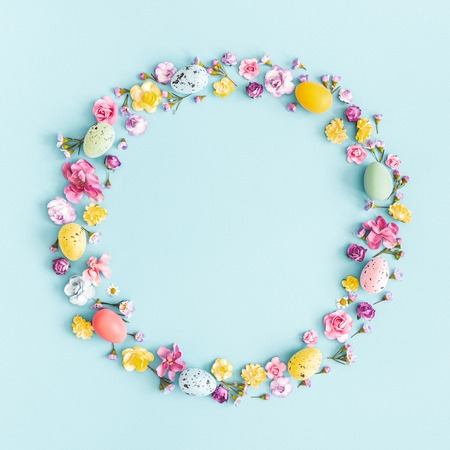 Easter eggs, colorful flowers on pastel blue background. Spring, easter concept. Flat lay, top view, copy space, square