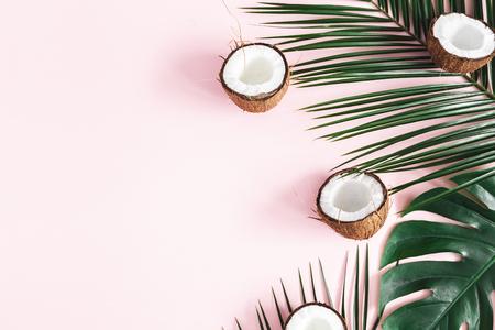 Foto de Summer composition. Tropical palm leaves, coconut onpastel pink background. Summer concept. Flat lay, top view, copy space - Imagen libre de derechos