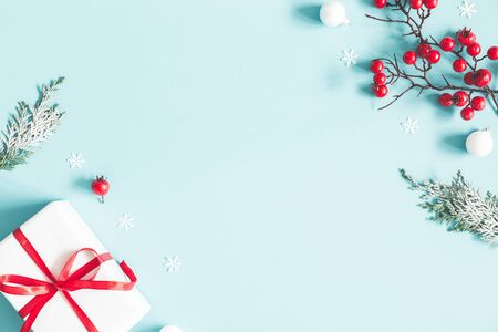 Foto de Christmas or winter composition. Frame made of gift, snowflakes, fir tree branches and red berries on pastel blue background. Christmas, winter, new year concept. Flat lay, top view, copy space - Imagen libre de derechos