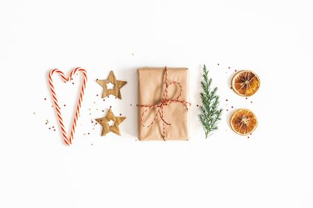 Foto de Christmas composition. Gift box, fir tree branches, golden decorations on white background. Christmas, winter, new year concept. Flat lay, top view - Imagen libre de derechos