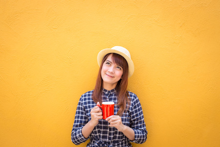 smiling woman wear in dress and hat holding red coffee cup on yellow cement wall background, thinking, imagination