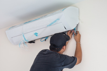 Photo for Man worker installs indoor air conditioner in the new home. Select focus - Royalty Free Image