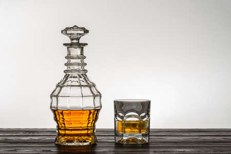 Photo pour Old style vintage whiskey decanter and a glass on wooden table - image libre de droit