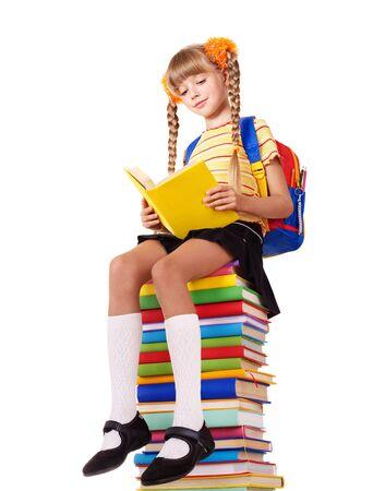 Schoolgirl sitting on pile of books. Isolated.