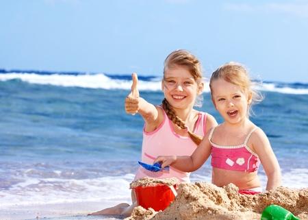 Foto de Little girl  playing on  beach. - Imagen libre de derechos