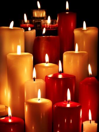 Foto de Group of burning candles on  black background. - Imagen libre de derechos