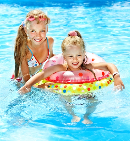 Photo pour Children sitting on inflatable ring in swimming pool. - image libre de droit