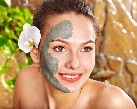 Beautiful girl having clay facial mask apply by beautician.