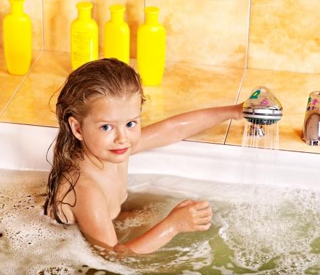 Happy child bathing in bubble bath .