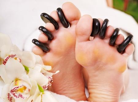 Woman receiving hot stone massage on feet.