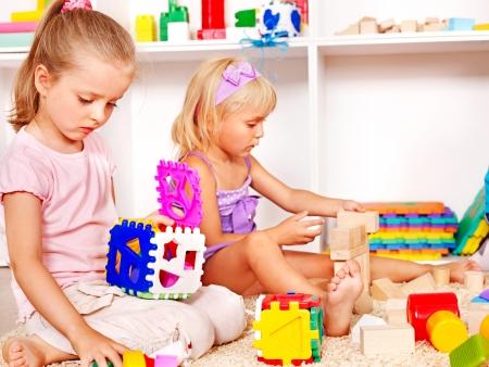 Foto de Children in kindergarten stacking block. - Imagen libre de derechos
