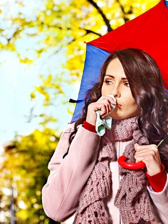 Woman sneezing handkerchief fall outdoor.