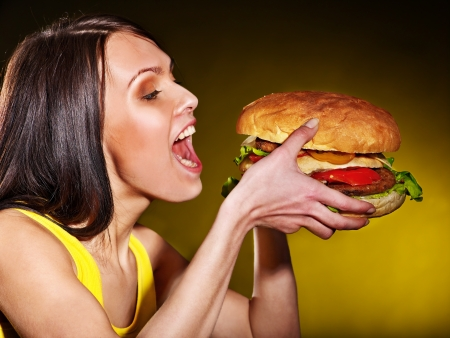 Slim woman eating hamburger.