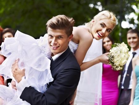 Groom carries his bride over shoulder. Outdoor.