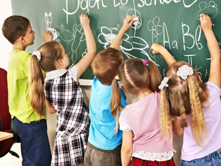 Photo for Children writing on blackboard at school. - Royalty Free Image