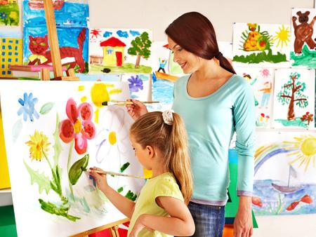 Happy children  with teacher painting.